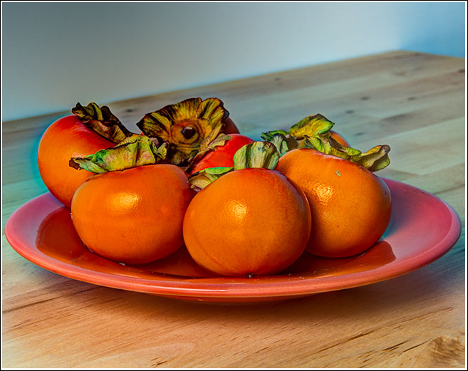 Persimmons on a salmon coloured plate